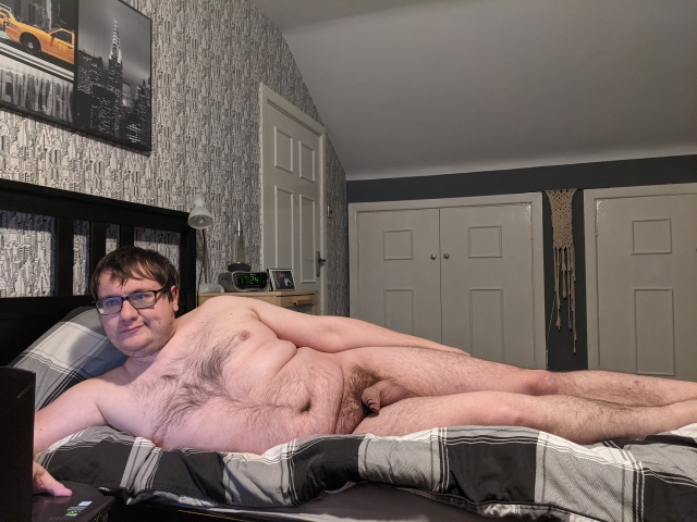 Nude selfie on my bed looking at my laptop.